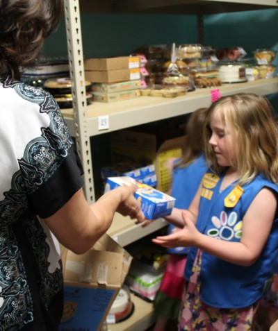 Girls Scouts stack food pantry shelves with cookies.