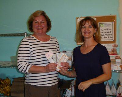 100 Women Who Care - Gainesville Chapter, present HRFP Director Eileen Smith with checks for $4,300.